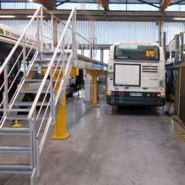 Adjustable walkway platform with stairs used for bus maintenance.