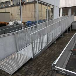 Angled wheelchair ramp in aluminium for building access.