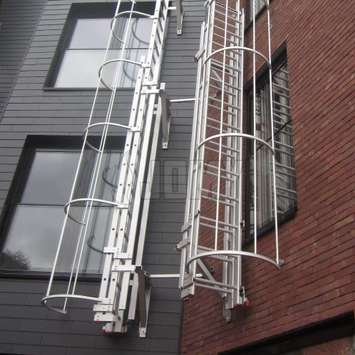 Drop-down ladder perpendicular to wall with a cage for fire evacuation.