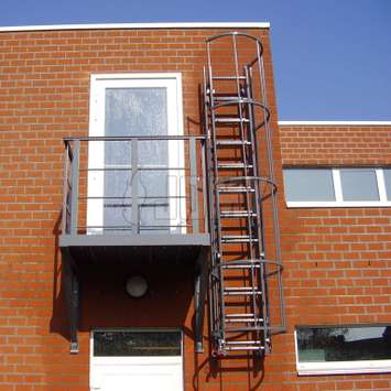 RAL colored drop-down ladder for fire evacuation with access balcony.