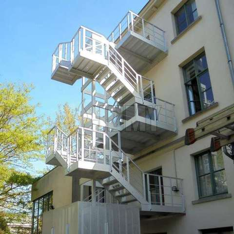 Aluminum Stairs Made For Egress And Access And Placed Outside Of A Medium  Sized Building.