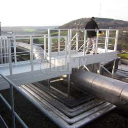 Aluminium walkway on a flat roof and used to walk over a pipe to a metal stair.