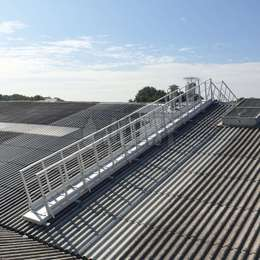 Inclined walkway with guardrails used on a factory roof.