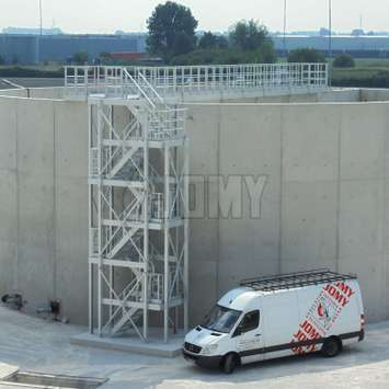 3 storey industrial stairs and platform for accessing a concrete storage tank in an industrial plant.
