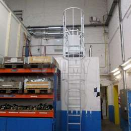 Cage ladder used to access the top of a mezzanine in a facility.