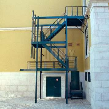 Black raisable evacuation stairs installed in a pedestrian alley at the back of a building.