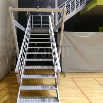 Retractable stairs with cable and pulley system in a gym.