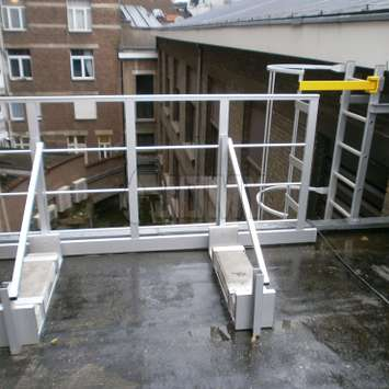 Safety guardrail with ballast for accessing a cage ladder on a roof.