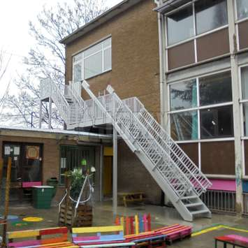 Fire escape stairs with a retractable flight installed in a school courtyard.