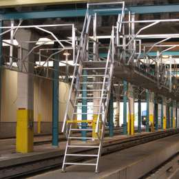 Industrial ship ladder for walkway platform access in a train maintenance workshop depot.