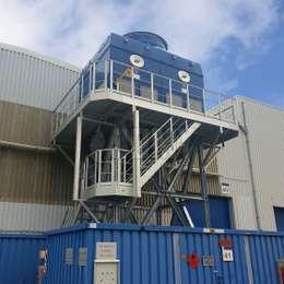 Walkway platform with stairs on tower structure for industrial machine maintenance.